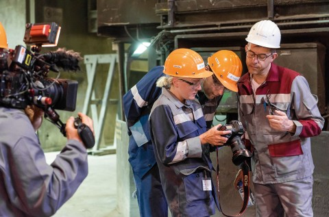 Auto newspaper journalist Markus Schönfeld, auto newspaper photographer Daniela Loof, and Mark Stagge of thyssenkrupp Steel look at the camera's display and examine the photographed motif.